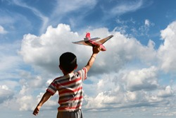 happy boy running airplane model under blue sky.