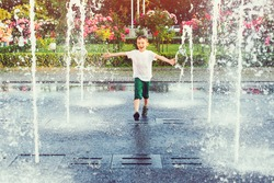 Happy boy running between water jets in city fountain. Summer in the city. Cute kid playing in a fountain with water. Child having fun in fountain. Summer vacation. Happy childhood.