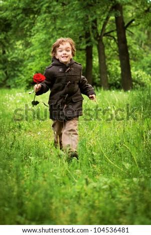 Happy boy running on grass, park - stock photo