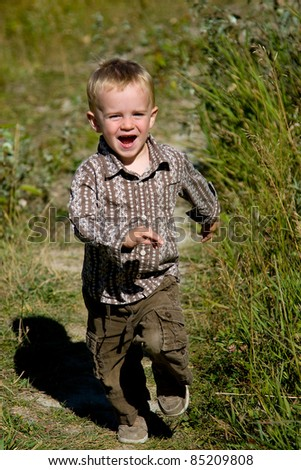 Happy boy running outdoors