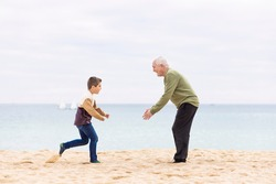Happy boy running to hug his grandfather on the beach