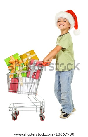 Happy boy shopping for christmas with a trolley full of presents - isolated