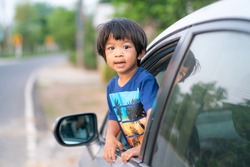 Happy boy showing face travel by car in village road. Summer road trip concept