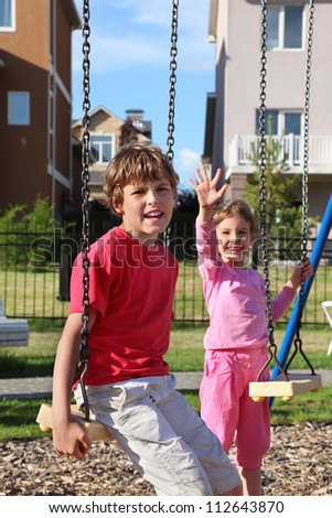 Happy boy sit on swing and girl waves her hand near cottage at sunny day. Focus on boy. - stock photo