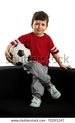 Happy boy sits with the soccer ball