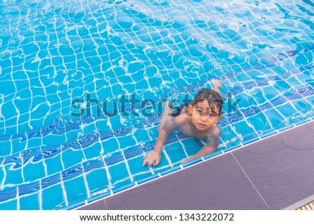 831810c05 Happy boy sitting around swimming pool and looking her sister. Swimming pool  class learning to