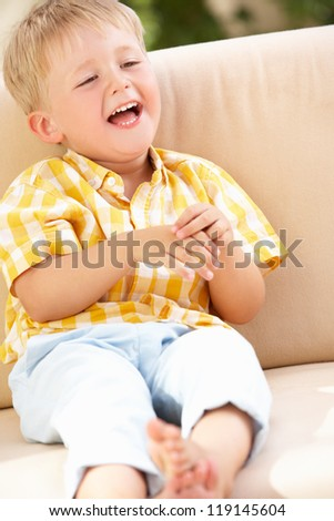 Happy Boy Sitting On Sofa - stock photo