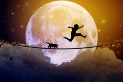 Happy boy teenager and cat jumping on a tight rope above clouds with moonlight moon background. Happiness friendship care free concept. Elements of this image furnished by NASA