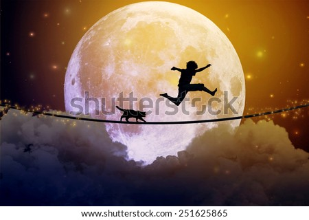 Photo of Happy boy teenager and cat jumping on a tight rope above clouds with moonlight moon background. Happiness friendship care free concept. Elements of this image furnished by NASA
