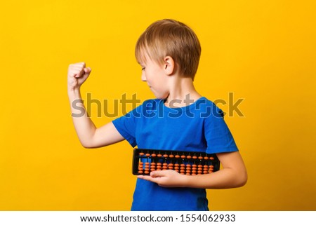 Happy boy trains his brain with abacus. Mental arithmetic school. Boy using abacus calculation. Everyday workouts make you strong. Strong mind in strong body.