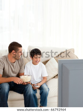 Happy boy watching television with his father on the sofa at home