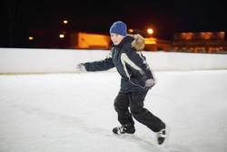Happy boy wearing in black suit skates at dark winter night.