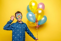 Happy boy with aquagrim on birthday party, colorful tiger holding colorful balloons isolated on yellow background.