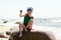 Happy boy with big smile on the rock holding a stone found in the beach. Real sea background. Summer activities for children. Holiday theme.
