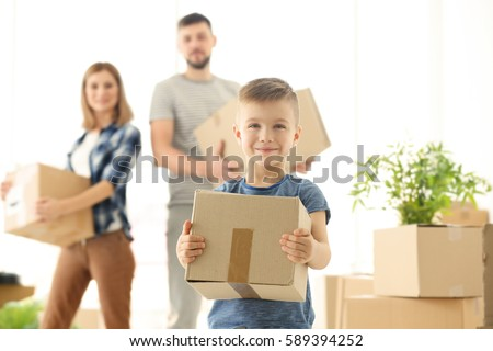 Happy boy with box on blurred background. Moving concept #589394252