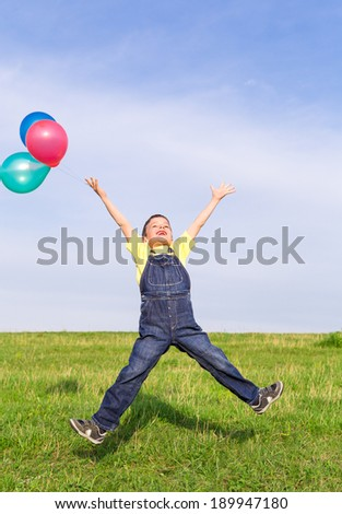 Happy boy with colorful balloons jumping on green field, outdoors
