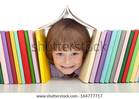 Happy boy with colorful books and a big grin - isolated