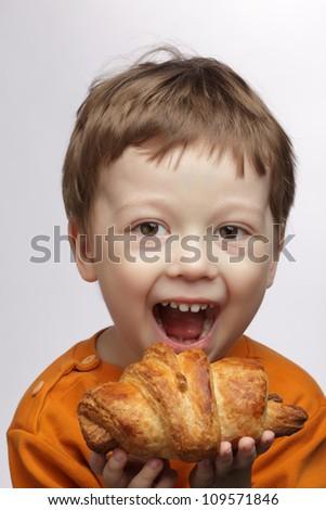 happy boy with  croissant - stock photo