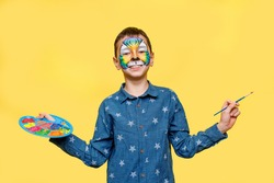 Happy boy with faceart on birthday party, colorful tiger holding palette with gouache isolated on yellow background.