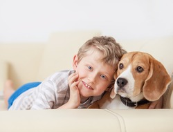 Happy boy with his dog lying on sofa