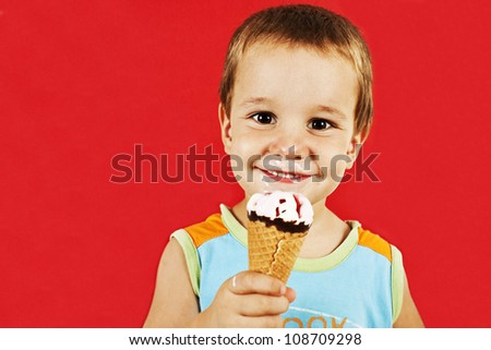 Happy boy with ice cream cone. Isolated on red background.