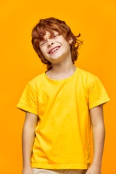 Happy boy with red hair in a yellow T-shirt on an isolated background