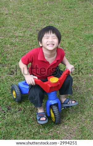 Happy boy with red shirt riding bicycle at the field
