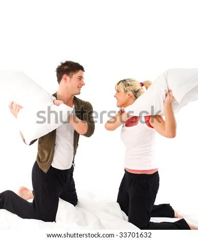 Happy boyfriend and girlfriend having a pillow fight