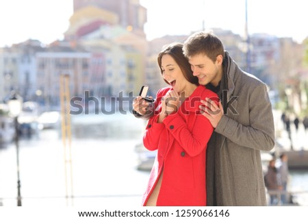 Happy boyfriend asking marry to his glad girlfriend in a coast town in winter