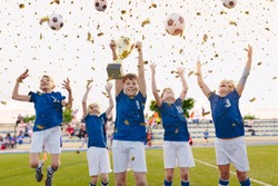 Happy Boys Celebrating Soccer Championship. Youth Football Winning Team Jumping and Rising Golden Cup on Trophy Ceremony After the Final Tournament Game. Football Stadium and Fans in the Background