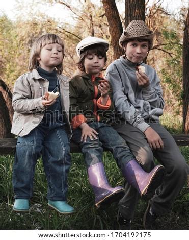 Happy boys eat buns outdoors summer piknik Stok fotoğraf ©