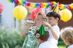 Happy boys with colorful hats making soap bubbles during outdoor birthday party