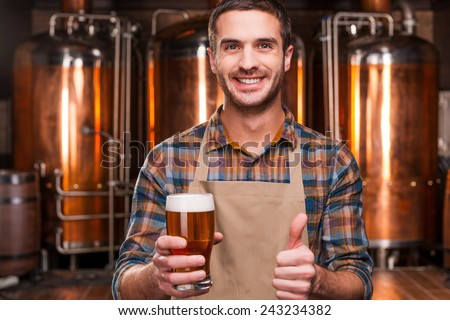 Happy brewer. Happy young male brewer in apron holding glass with beer and looking at it with smile while standing in front of metal containers