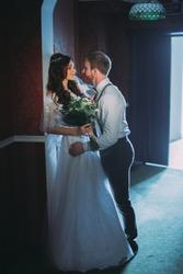 Happy bride and bearded groom on the wedding walk in the modern hotel hall on wedding