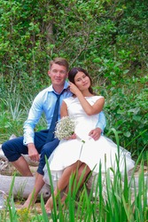 Happy bride and beautiful groom sitting against green background