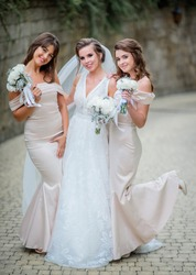Happy bride and bridesmaids hold white wedding bouquets posing on the backyard