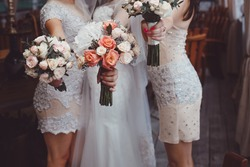 Happy bride and bridesmaids holding bouquets, posing