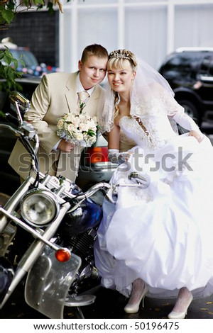 Happy bride and groom about stylish motorcycle