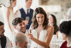Happy bride and groom are socialising with the guests at their wedding reception.