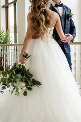 Happy bride and groom dancing indoors at wedding day, copy space. Wedding couple in love, newlyweds. Wedding concept