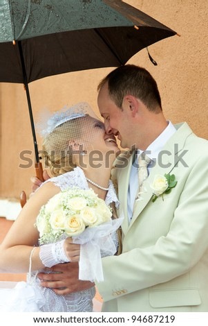 Happy bride and groom embracing under an umbrella