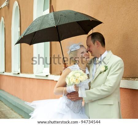 Happy bride and groom embracing under an umbrella