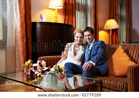 Happy bride and groom in interior of hotel room in wedding day