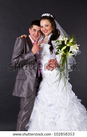 Happy bride and groom in studio - stock photo