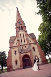Happy bride and groom kissing in front of a church