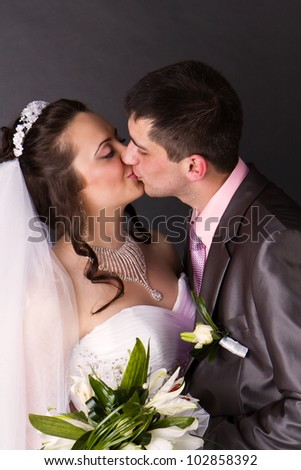 Happy bride and groom kissing in studio