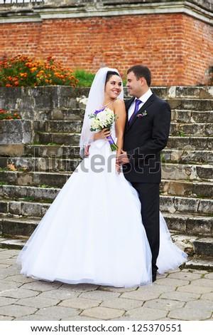 Happy bride and groom near ancient ladder at wedding walk