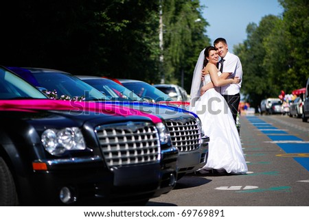 Happy bride and groom near wedding limousines on romantic walk