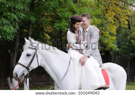 Happy bride and groom on a horse