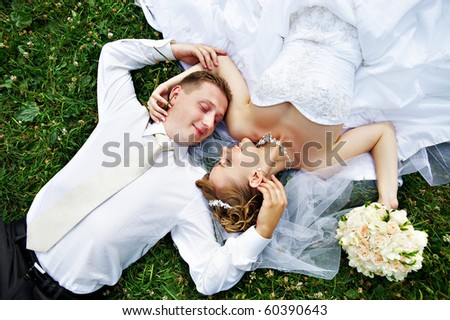 Happy bride and groom on grass in park